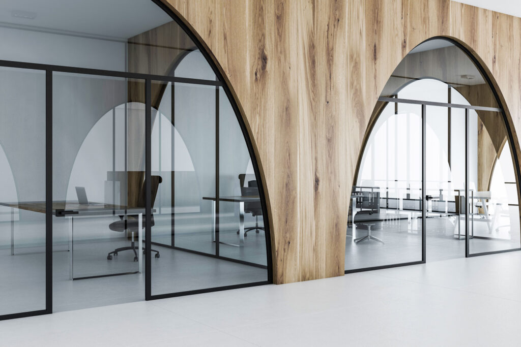 White and wooden office with a white floor, arched doorways and computer tables with black chairs standing near it. 3d rendering mock up